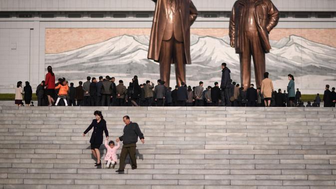 Sebuah keluarga berjalan menuruni tangga setelah memberikan penghormatan di depan dua patung pemimpin Korea Utara sebelumnya (AFP)