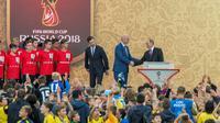 """Presiden Rusia Vladimir Putin berjabat tangan dengan Presiden FIFA, Gianni Infantino usai memperlihatkan trofi Piala Dunia dalam pembukaan upacara  """"FIFA World Cup Trophy Tour"""" di stadion Luzhniki di Moskow (9/9). (AFP Photo/Mladen Antonov)"""