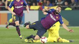 Striker Barcelona, Luis Suarez, terjatuh saat berebut bola dengan pemain Villarreal, Ramiro Funes Mori, pada laga La Liga 2019 di Stadion Ceramica, Selasa (2/4). Kedua tim bermain imbang 4-4. (AP/Alberto Saiz)