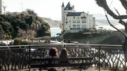 Dua wanita duduk di bangku selama cuaca musim dingin yang hangat di sepanjang garis pantai kota Biarritz di Perancis barat (17/2). Kota ini terletak di region Aquitane, Departemen Pyrénées-Atlantiques. (AFP Photo/Iroz Gaizka)