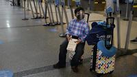 Alejandro Zelaya, 10, menunggu check-in untuk penerbangannya ke El Salvador di Bandara Internasional Los Angeles, 23 November 2020. Sekitar 1 juta orang Amerika memadati bandara dan pesawat menjelang libur Thanksgiving pekan ini bahkan saat kematian akibat COVID-19 melonjak. (AP Photo/Jae C. Hong)