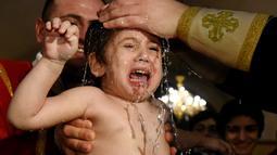 Seorang bayi menangis saat dibaptis dalam upacara pembaptisan massal di Gereja Katedral Holy Trinity, Tbilisi, Georgia (21/1). (AFP Photo/Vano Shlamov)
