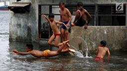Seorang anak melompat saat bermain di Masjid yang terkena Abrasi di kawasan Muara Baru, Jakarta, Kamis (4/1). Anak-anak yang bermukim di kawasan tersebut banyak menghabiskan waktu saat berlibur sekolah untuk bermain di laut. (Liputan6.com/Johan Tallo)