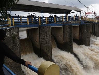 Warga melihat debit air di Bendung Katulampa, Bogor, Jawa Barat, Jumat (19/2/2021). Meski sempat mengalami kenaikan debit air pada Jumat (19/2) pagi, namum sekitar pukul 15.00 WIB, debit air di Bendung Katulampa berada di zona hijau dengan ketinggian sekitar 50 cm. (Liputan6.com/Helmi Fithriansyah)