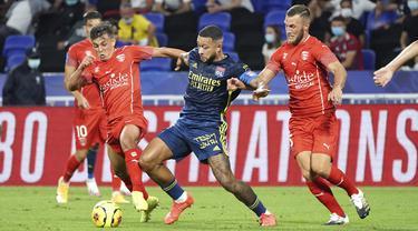 Penyerang Lyon, Memphis Depay, berebut bola dengan pemain Nimes pada laga lanjutan Liga Prancis di Stadion Groupama, Sabtu (19/9/2020) dini hari WIB. Lyon bermain imbang 0-0 atas Nimes. (AP Photo/Laurent Cipriani)
