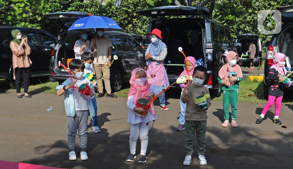 Para siswa TK memainkan miniatur bedug buatan mereka saat mengikuti proses pembelajaran secara Drive in Learning di area parkir Padepokan Pencak Silat Indonesia, Jakarta, Kamis (8/4/2021). Kegiatan ini untuk mengenalkan bulan suci Ramadan kepada anak-anak sedari dini. (Liputan6.com/Herman Zakharia)