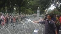 Sejumlah pedemo berusaha merusak barikade kawat berduri di sekitar Bundaran Patung Kuda, Silang Monas, Jakarta Pusat. (Radityo Proyasmoro/Liputan6.com)