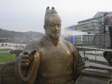 Pekerja membersihkan patung perunggu Raja Sejong, raja Korea abad ke-15, selama acara pembersihan jalan dan taman untuk musim semi di Seoul (9/4). Raja Sejong terkenal karena jasanya di dalam menciptakan abjad Korea, Hangeul yang menggantikan penggunaan penulisan Hanja. (AFP Photo/Jung Yeon-Je)