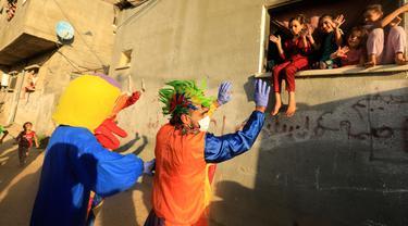 Badut dan seseorang yang mengenakan kostum bebek menghibur anak-anak Palestina, di tengah lockdown yang diberlakukan oleh otoritas setempat menyusul lonjakan kasus virus corona, di Khan Younis, Jalur Gaza selatan pada Rabu (2/9/2020). (MAHMUD HAMS/AFP)