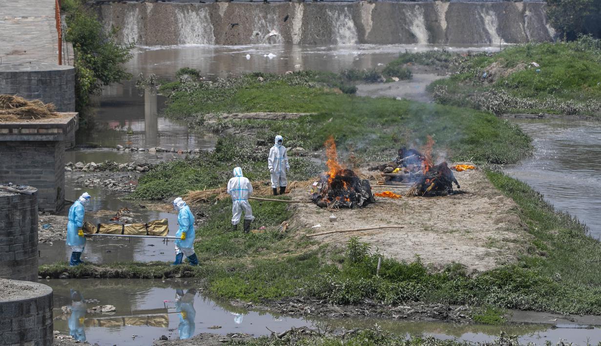 Petugas mengenakan pakaian pelindung membawa jenazah korban COVID-19 untuk dikremasi di tepi Sungai Bagmati dekat kuil Pashupatinath, Kathmandu, Nepal (3/5/2021). Lonjakan infeksi di Nepal telah mendorong pemerintah memberlakukan lockdown baru di kota besar dan kecil. (AP Photo/Niranjan Shrestha)