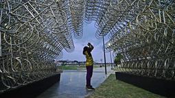 Seorang pria mengambil gambar instalasi seni seniman China Ai Weiwei yang berjudul 'Forever Cycles' di Rio de Janeiro, Brasil, Senin (19/8/2019). Instalasi Ai Weiwei ini akan dibuka pada 21 Agustus 2019. (CARL DE SOUZA/AFP)