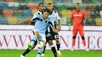 Penyerang Lazio, Ciro Immobile, berebut bola dengan bek Udinese, Rodrigo Becao, pada laga lanjutan Serie A pekan ke-33 di Dacia Arena, Kamis (16/7/2020) dini hari WIB. Lazio bermain imbang 0-0 atas Udinese. (AFP/Miguel Medina)