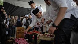 Hatta Rajasa menaburkan bunga di makam almarhum Adara Taista di makam TPU Tanah Kusir, Jakarta, Senin (21/5). Rasyid Rajasa dan Adara Taista baru menikah selama enam bulan. (Liputan6.com/Faizal Fanani)