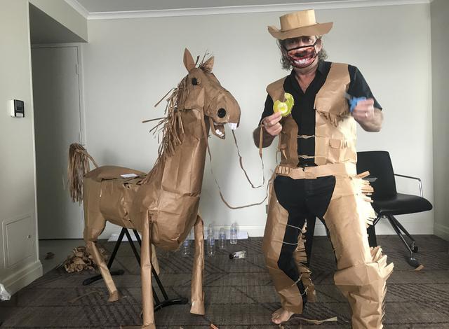 David Marriott berpose dengan kuda kertasnya Russell di kamar hotelnya di Brisbane, Australia, 1 April 2021. Direktur seni di iklan TV itu juga membuat pakaian koboi, celana topi dan juga rompi kantong kertas makanannya yang dikirimkan selama menjalani karantina. (David Marriott via AP)