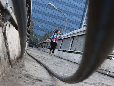 Pejalan kaki melintasi jembatan penyeberangan orang tanpa atap dan tidak terawat di Jalan TB Simatupang, Jakarta, Rabu (10/10). Kondisi tersebut menyebabkan JPO terkesan kumuh serta mengurangi kenyamanan pejalan kaki. (Liputan6.com/Immanuel Antonius)