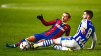 Penyerang Barcelona, Antoine Griezmann, berebut bola dengan pemain Real Sociedad, Mikel Merino, pada laga semifinal Piala Super Spanyol di Stadion Nuevo Arcangel, Rabu (13/1/2021). Barcelona menang adu penalti dengan skor 3-2. (AP/Jose Breton)