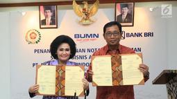 Direktur Hub. Kelembagaan Bank BRI Sis Apik Wijayanto dan Ketum Dharma Pertiwi Nanny Hadi Tjahjanto menunjukkan Nota Kesepahaman Layanan Jasa Keuangan Perbankan melalui Agen BRILink, di Jakarta, (15/4). Bank BRI berpartisipasi aktif mengimplementasi program inklusi keuangan. (Liputan6.com/HO/Roni)