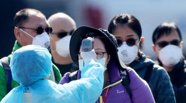Petugas memeriksa suhu tubuh penumpang asing yang turun dari kapal pesiar Diamond Princess yang dikarantina di Yokohama, Jepang, Jumat (21/2/2020).