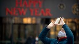 Seorang pria mengenakan masker saat mengambil foto dekorasi perayaan Imlek Tahun Tikus Logam di Beijing, 22 Januari 2020. Otoritas kesehatan China mendesak orang-orang menghindari keramaian dan pertemuan publik di Wuhan, kota yang menjadi pusat penyebaran wabah virus corona. (AP/Mark Schiefelbein)