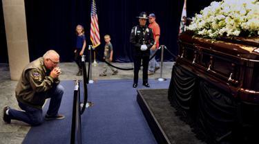 Pengunjung Steven Leslie berdoa di depan peti mati mantan Ibu Negara Nancy Reagan di Perpustakaan Kepresidenan Ronald Reagan, Simi Valley, California (9/3). Nancy Davis Reagan lahir 6 Juli 1921 di New York City. (REUTERS/Wally Skalij)