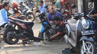 Mekanik memperbaiki motor di salah satu bengkel di Otista, Jakarta, Minggu (10/6). Calon pemudik motor mulai memenuhi bengkel guna menyervis atau mengganti suku cadang kendaraan sebelum digunakan untuk mudik Lebaran. (Liputan6.com/Angga Yuniar)