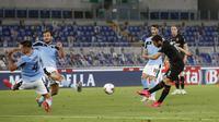 Pemain AC Milan Hakan Calhanoglu (kanan) mencetak gol ke gawang Lazio pada pertandingan Serie A di Olympic Stadium, Roma, Italia, Sabtu (4/7/2020). AC Milan mengalahkan Lazio dengan skor 3-0. (AP Photo/Riccardo De Luca)