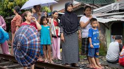Warga melihat proses evakuasi KRL yang anjlok di kawasan Kebon Pedes, Bogor, Jawa Barat, Minggu (10/3). Penanganan KRL anjlok dilakukan dengan menggunakan crane yang didatangkan dari Bandung. (Liputan6.com/Immanuel Antonius)