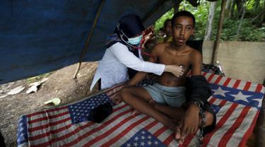Dokter memeriksa kesehatan Deden, remaja yang dirantai di pohon oleh keluarganya di desa Longkewang, Serang, Banten, Indonesia (23/3). Tahun ini Indonesia mengirimkan tim medis untuk membantu pasien yang mengalami ganguan mental. (REUTERS/Beawiharta)