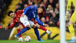 Gelandang Liverpool, Takumi Minamino berusaha merebut bola dari pemain Everton, Mason Holgate pada pertandingan babak ketiga Piala FA di Anfield, Minggu (5/1/2020). Minamino bermain selama 70 menit, lalu digantikan Alex Oxlade-Chamberlain. (AFP/Paul Ellis)