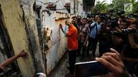 Tersangka penampung TKI Ilegal bersiap masuk ke dalam rumah di Jalan Percetakan Negara X, Jakarta, Rabu (31/5). Bersama satu tersangka, petugas Dirtipidum Mabes Polri melakukan pencarian barang bukti baru. (Liputan6.com/Helmi Fithriansyah)