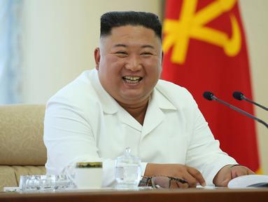 Pemimpin Korea Utara, Kim Jong-un berbicara selama pertemuan politbiro ke-13 dari Partai Buruh di lokasi yang dirahasiakan dalam gambar yang dirilis Senin (8/6/2020). Dalam pertemuan itu, Kim Jong-un juga membahas proyek-proyek ekonomi termasuk industri kimia. (Photo by STR / KCNA VIA KNS / AFP)