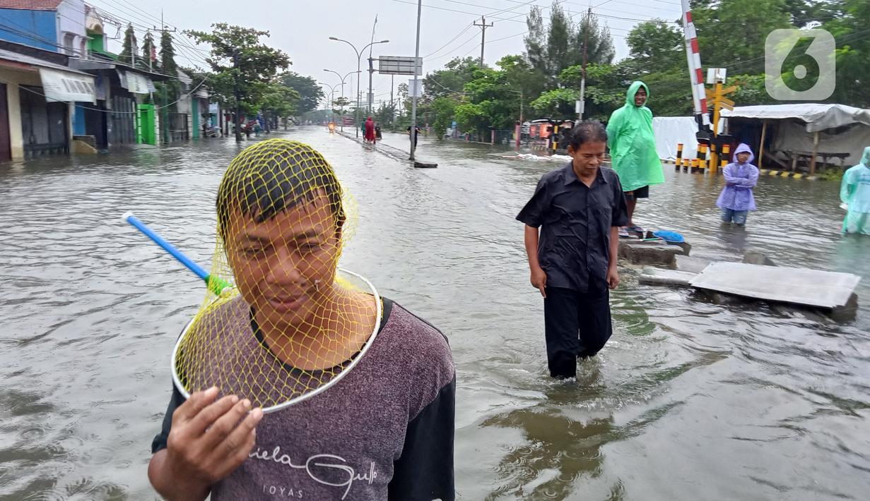 Aktivitas warga saat banjir menggenangi daerah Kaligawe, Kota Semarang, Selasa (9/2/2021). Banjir yang menggenangi daerah Kaligawe sejak beberapa hari lalu hingga Selasa (9/2) pagi masih belum surut dan mengakibatkan mobilitas warga menjadi terhambat. (Liputan6.com/Gholib)