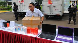 Petugas membawa barang bukti produk elektronik ilegal saat konferensi pers di Kantor Pusat Bea Cukai, Jakarta, Selasa (30/4/2019). Selama April 2019, Dirjen Bea dan Cukai Kemkeu menyita produk elektronik ilegal dengan total nilai barang mencapai Rp 61,86 miliar. (Liputan6.com/Angga Yuniar)