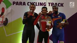 Pebalap sepeda Indonesia, M. Fadli Imammuddin  bersama pebalap Malaysia Mohd Najib dan Singh Harinder dari India mengigit medali usai bertanding  pada nomor 4000 meter individual pursuit C4, Jakarta Timur, Jumat (12/10). (Merdeka.com/Imam Buhori)