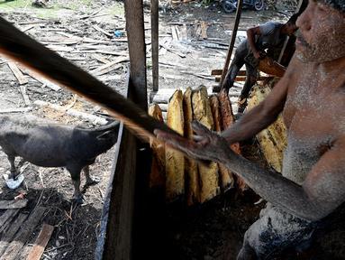 Pekerja mengolah bahan dari pohon sagu di sebuah desa di Labuhan Haji, provinsi Aceh selatan (26/10/2021). Pohon Sagu, atau Rumbia, banyak tumbuh di berbagai wilayah di Indonesia. (AFP/Chaideer Mahyuddin)