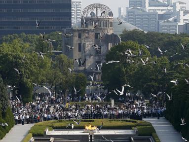 Burung Merpati terbang di atas Peace Memorial Park, dengan latar Monumen Bom Atom, pada saat upacara peringatan 70 tahun jatuhnya bom atom di Hiroshima, Jepang (6/8/2015). 140.000 penduduk Jepang tewas akibat Bom Atom. (REUTERS/Toru Hanai)