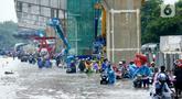 Pengendara mendorong motornya melintasi banjir di Jalan Raya Bekasi, Jakarta Timur, Selasa (25/2/2020). Banjir akibat hujan yang melanda Bekasi sejak Selasa (25/2) dini hari memutus beberapa titik jalan raya di wilayah setempat. (merdeka.com/Imam Buhori)