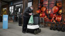 Pekerja toko Co-op memuat tas ke dalam robot otonom bernama Starship saat mengirimkan bahan makanan di Milton Keynes, Inggris, 20 September 2021. Robot Starship bertugas mengantarkan belanja dan makanan. (DANIEL LEAL-OLIVAS/AFP)