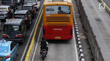 Pengendara sepeda motor berada di belakang bus Transjakarta di Jalan Gunung Sahari, Jakarta, Kamis (27/12). Selain melanggar hukum, perilaku buruk pemotor tersebut juga dapat membahayakan keselamatan. (Liputan6.com/Immanuel Antonius)