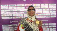 Pecatur Indonesia peraih dua medali emas di Asian Para Games 2018, Debi Ariesta, berpose dengan medalinya di GOR Cempaka Putih, Jakarta, Rabu (10/10/2018). (Bola.com/Benediktus Gerendo Pradigdo)