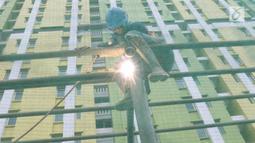 Pekerja tengah mengelas saat menyelesaikan pembangunan JPO Pasar Rumput di Jakarta, Selasa (15/1). Pembangunan jembatan di bangunan pasar yang terintegrasi dengan rusun tersebut dibuat untuk memudahkan mobilitas warga. (Liputan6.com/Immanuel Antonius)