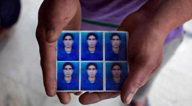 Vijay Kumar menampilkan foto adik laki-lakinya Indrajit Kumar yang jasadnya ditemukan terkubur di barat laut Mosul, India (21/3). Sebanyak 39 warga India yang diculik oleh Kelompok ISIS pada 2014 dikonfirmasi telah tewas. (AP/Ashwini Bhatia)