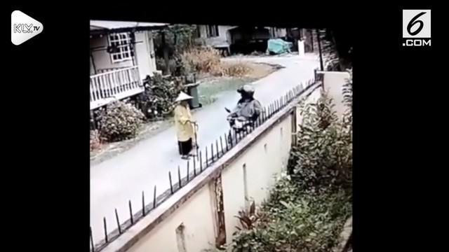 Seorang pengendara motor tertangkap kamera sedang menjambret seorang lansia.