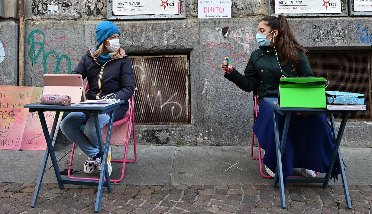 Anita Iacovelli (kiri) dan temannya Lisa Rogliatti, berusia 12 tahun, duduk di depan sekolah Italo Calvino di Turin, Italia, 17 November 2020. Anita memprotes penutupan sekolahnya karena pembatasan COVID-19 dengan duduk di luar gedung sambil mengikuti pelajaran jarak jauh. (Miguel MEDINA/AFP)