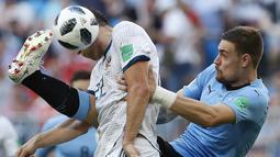 Pemain Uruguay, Sebastian Coates (kanan) menghalau bola dari sundulan pemain Rusia, Artyom Dzyuba pada laga grup A Piala Dunia 2018 di Samara Arena, Samara, Rusia, (25/6/2018). Uruguay menang 3-0. (AP/Hassan Ammar)