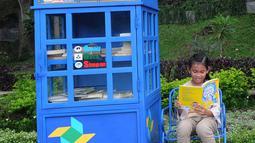 Seorang anak membaca buku yang ada di layanan Kotak Literasi Cerdas (Kolecer) di Taman Sempur, Bogor, Jawa Barat, Kamis (20/12). Selain menumbuhkan budaya literasi, Kolecer juga diharap mampu meningkatkan minat baca masyarakat. (Merdeka.com/Arie Basuki)