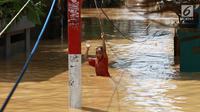 Seorang anak melintasi banjir yang menggenangi kawasan Pejaten Timur, Jakarta, Jumat (26/4). Banjir yang berasal dari luapan Sungai Ciliwung tersebut merendam ratusan rumah warga hingga kedalaman lebih dari satu meter. (Liputan6.com/Immanuel Antonius)