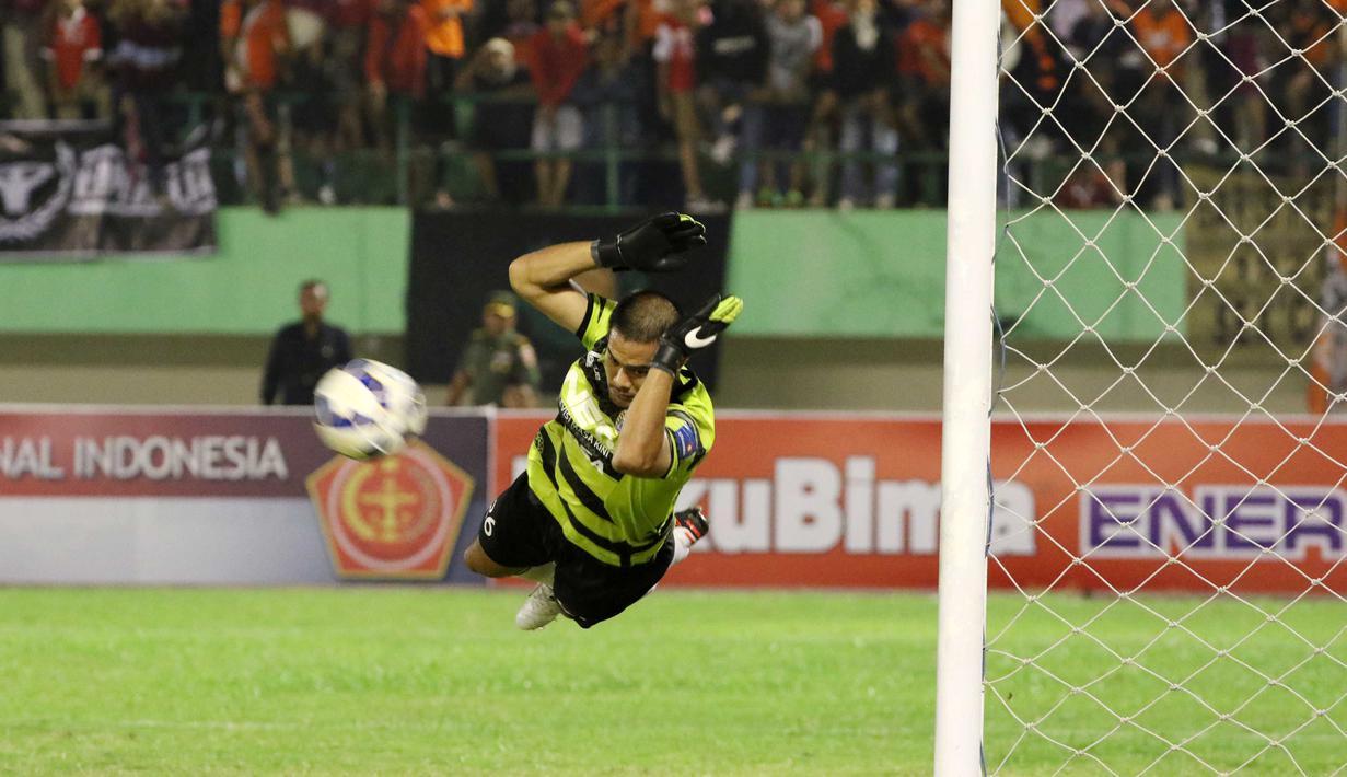 Kiper Persija, Andritany terbang menghalau bola pada laga Piala Jenderal Sudirman di Stadion Manahan, Solo, Selasa (15/12/2015). (Bola.com/Nicklas Hanoatubun)