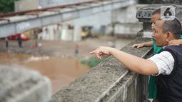 Warga mengamati banjir yang menggenangi kawasan Rawajati dari atas flyover di Jakarta Timur, Rabu (1/1/2020). Banjir yang berasal dari luapan Sungai Ciliwung itu menjadi daya tarik tersendiri bagi sebagian pemotor yang melintasi di flyover tersebut. (Liputan6.com/Immanuel Antonius)
