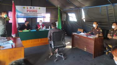 Salah satu pelanggar PPKM Darurat tengah mengikuti jalannya sidang Tipiring di tenda Posko penegakan hukum PPKM Darurat di bilangan Simpang Lima, Garut, Jawa Barat.